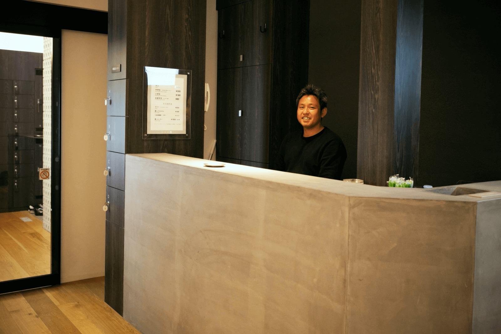 改良湯フロントに座る大和伸晃さん