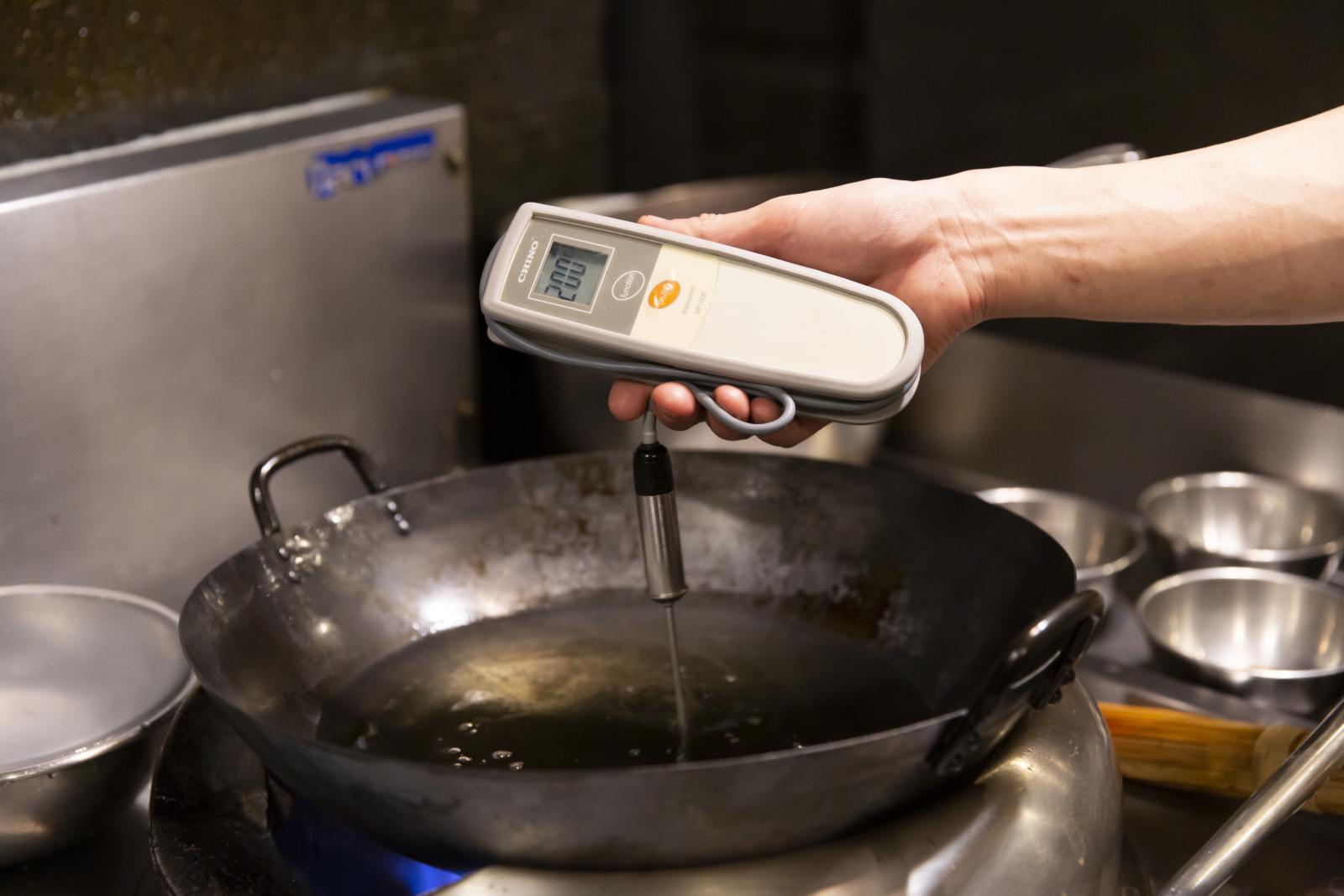 油を温度計ではかる様子