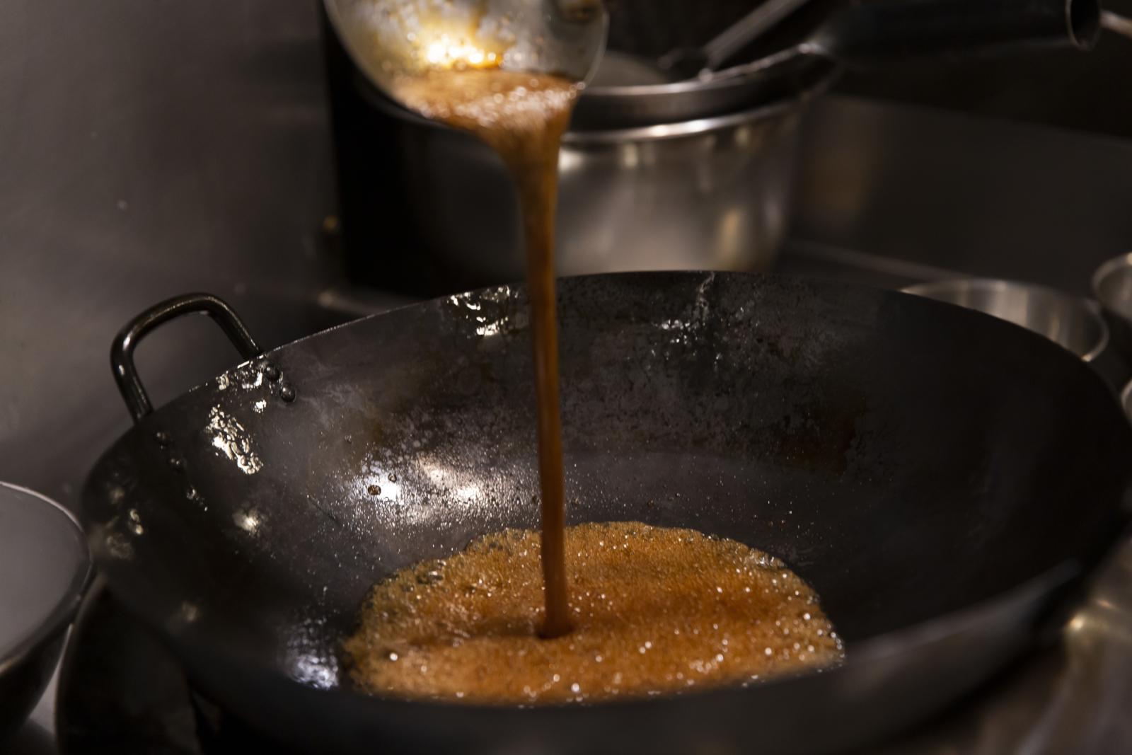 タレと片栗粉を中華鍋で火にかける